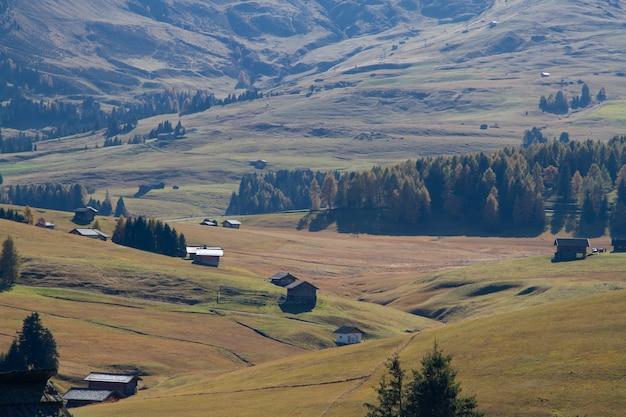 Hoge hoek die van gebouwen op met gras begroeide heuvels in dolomiet italië is ontsproten