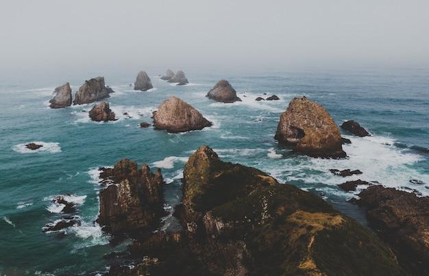 Hoge hoek die van grote rotsen in nugget point ahuriri, nieuw-zeeland met een mistige achtergrond is ontsproten