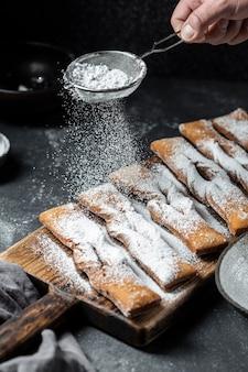 Hoge hoek die van hand poedersuiker op desserts zeven