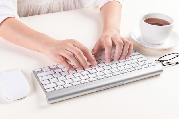 Hoge hoek die van handen is ontsproten die op een toetsenbord typen