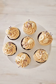 Hoge hoek die van heerlijke chocoladecupcakes met wit roomtopping is ontsproten