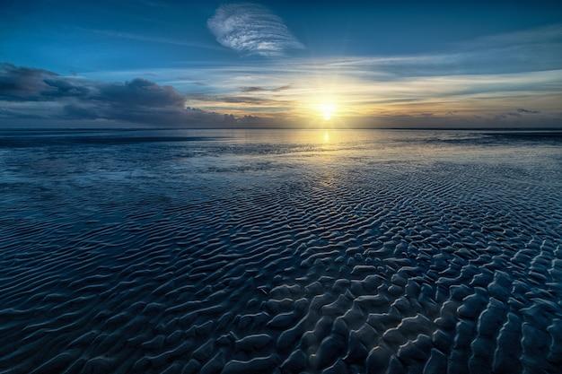 Hoge hoek die van het oceaanwater en de zon is ontsproten die aan de horizon schijnt