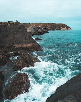 Hoge hoek die van overzeese golven is ontsproten die de rotsen met een bewolkte hemel raken