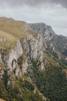 Hoge hoek die van rotsachtige bergen in vlasic, bosnië is ontsproten op een sombere dag