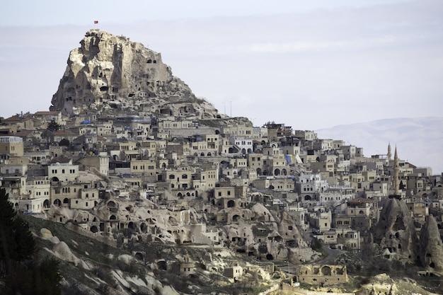 Hoge hoek die van uchisar-kasteel in cappadocia, turkije onder de bewolkte hemel is ontsproten