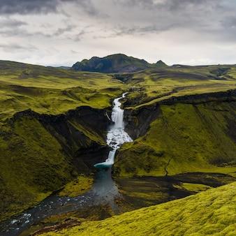 Hoge hoek die van watervallen in hooglandengebied van ijsland met een bewolkte grijze hemel is ontsproten