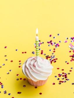 Hoge hoek eenvoudige verjaardag muffin en confetti