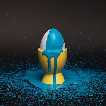 Hoge hoek ei op steun met blauwe verf