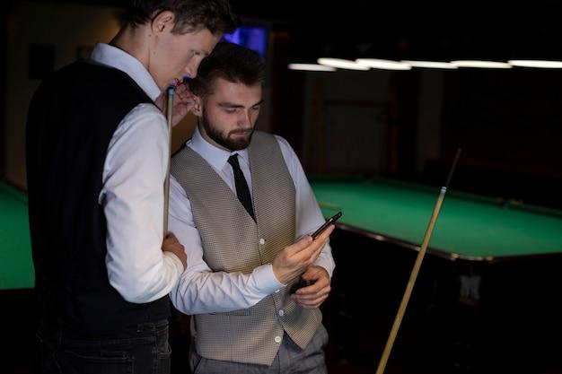 Hoge hoek elegante jongens kijken naar smartphone
