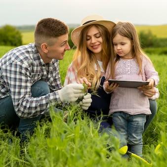 Hoge hoek familie op boerderij met tablet