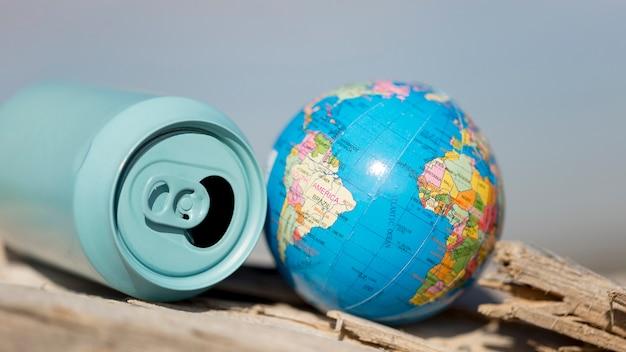 Hoge hoek frisdrankblikje naast kleine wereldbol