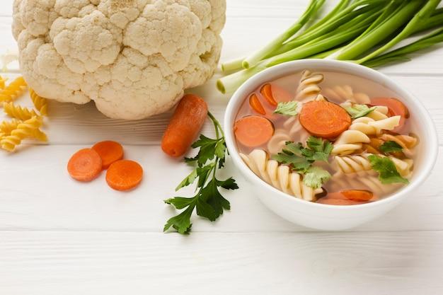 Hoge hoek fusilli broccoli en wortelsoep in kom