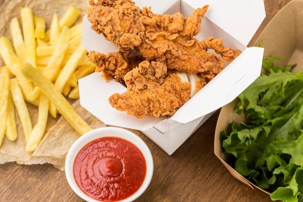 Hoge hoek gebakken kip en frietjes met ketchup
