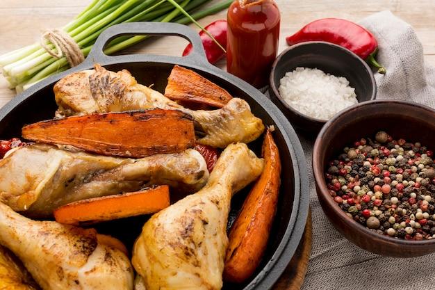 Hoge hoek gebakken kip en groenten in pan met kruiden