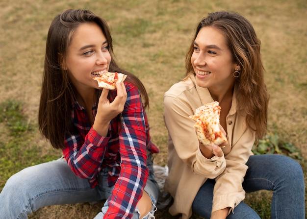Hoge hoek gelukkige meisjes die pizza eten
