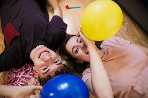 Hoge hoek gelukkige tieners die op de vloer leggen