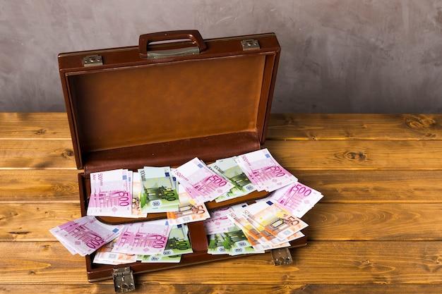 Hoge hoek geopende koffer met geld