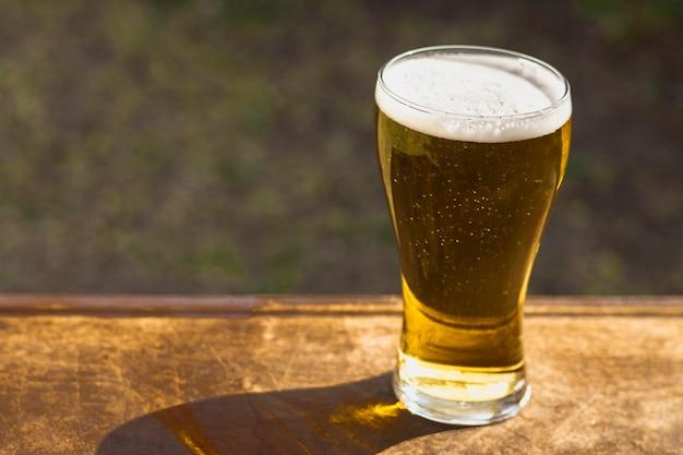 Hoge hoek glas met schuimend bier op tafel
