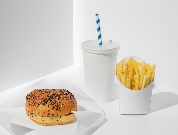 Hoge hoek hamburger en frietjes in verpakking met lege beker