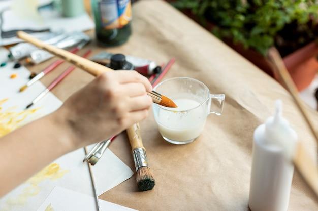 Hoge hoek hand met schilderij borstel