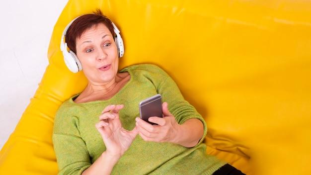 Hoge hoek hogere vrouw gelegde het luisteren muziek