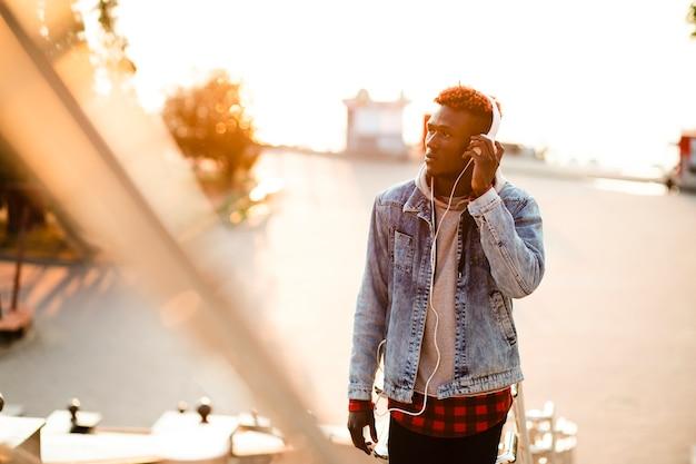 Hoge hoek jonge man in stad luisteren muziek