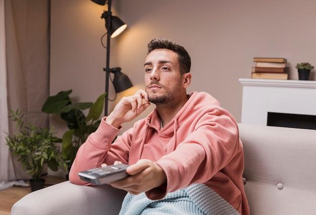 Hoge hoek jonge man met afstandsbediening