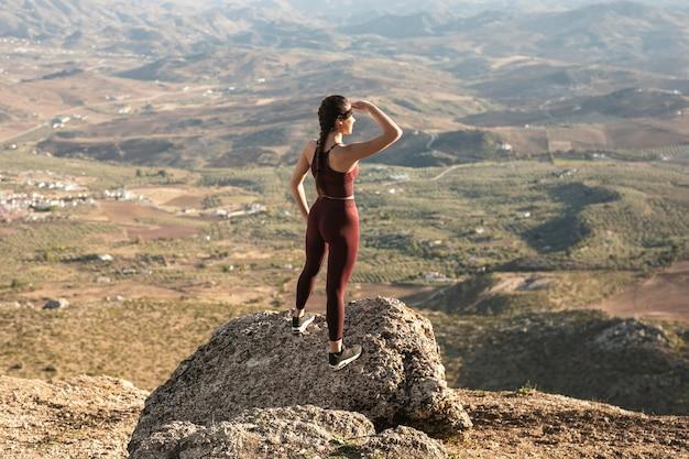 Hoge hoek jonge vrouw die op berg weg kijkt