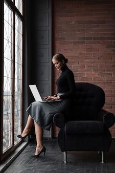 Hoge hoek jonge vrouw die op laptop werkt