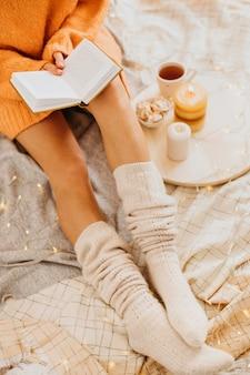Hoge hoek jonge vrouw genieten van de wintervakantie met een kopje thee