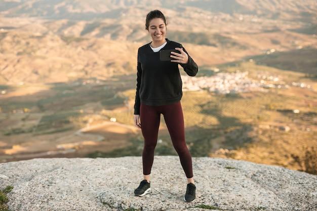 Hoge hoek jonge vrouw op berg die selfie neemt