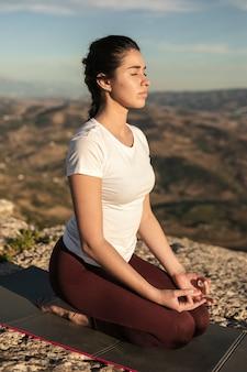 Hoge hoek jonge vrouw op mat mediteren