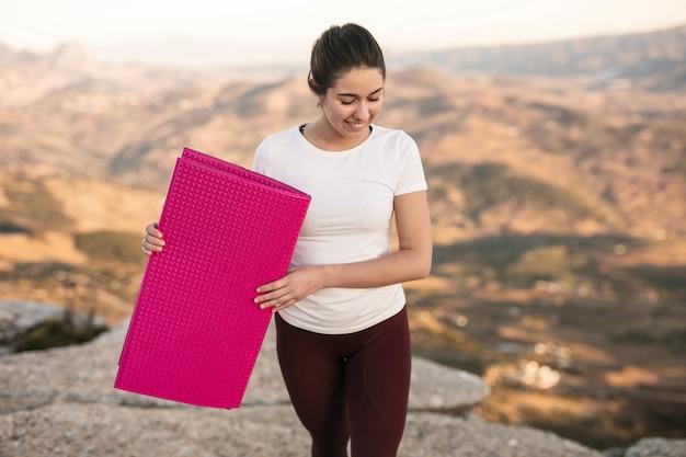 Hoge hoek jonge vrouwelijke dragende yogamat