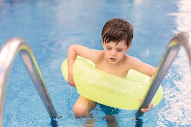Hoge hoek jongen in zwembad met vlotter