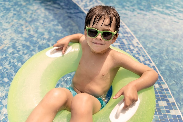 Hoge hoek jongen in zweven bij zwembad