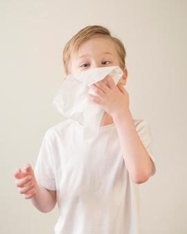 Hoge hoek jongen waait neus