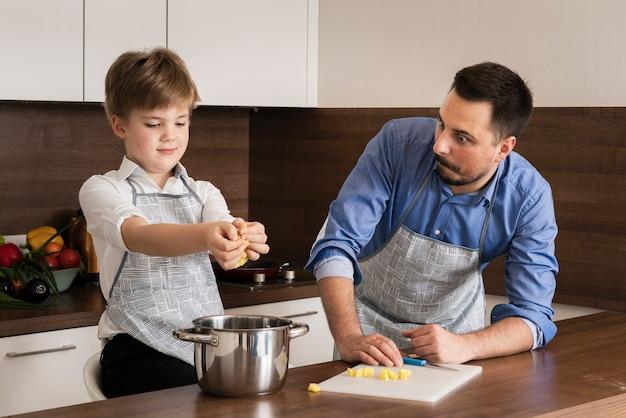 Hoge hoek jongetje met vader koken