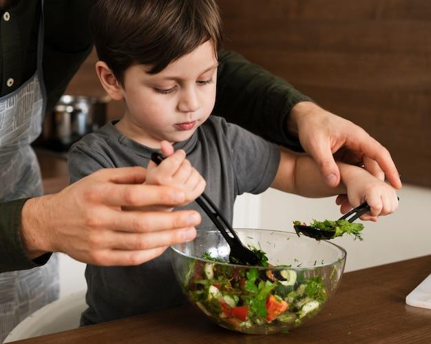 Hoge hoek jongetje salade mengen