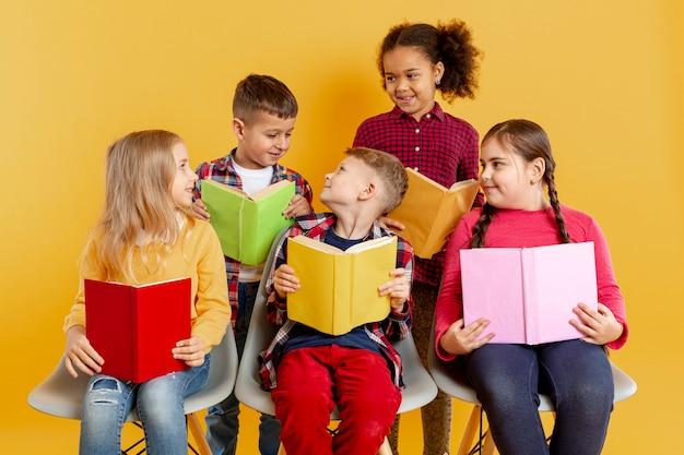 Hoge hoek kinderen met boeken kijken naar elkaar
