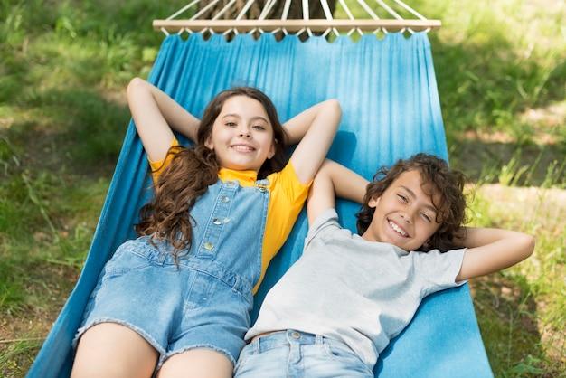 Hoge hoek kinderen zitten in een hangmat