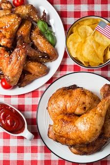 Hoge hoek kippenpoten en vleugels met frietjes