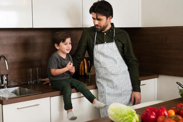 Hoge hoek kleine jongen en vader in keuken