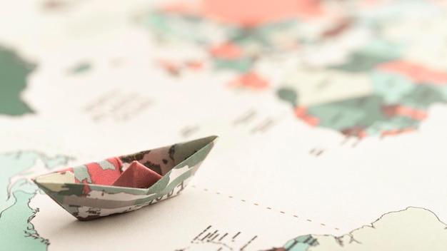 Hoge hoek kleine origami boot op wereldkaart