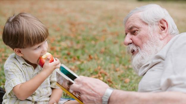 Hoge hoek kleinzoon en opa in park