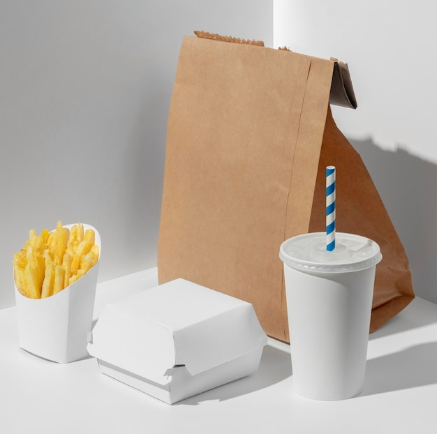 Hoge hoek lege fastfood beker met verpakking frietjes en blanco papieren zak