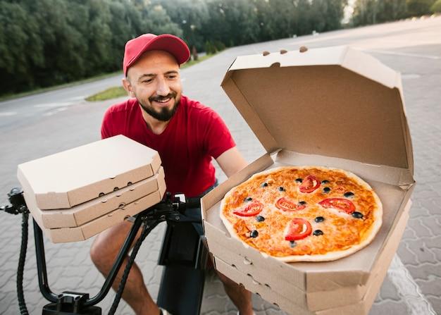 Hoge hoek levering man met geopende pizzadoos