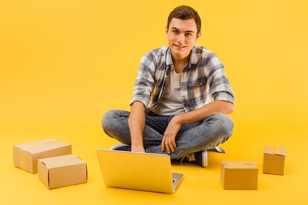 Hoge hoek leveringsmens met laptop en pakketten