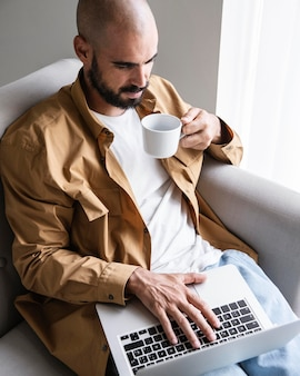 Hoge hoek man aan het werk op laptop
