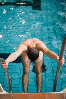 Hoge hoek man bedrijf uit zwembad trappen