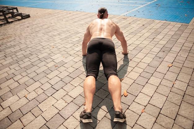 Hoge hoek man doet push ups